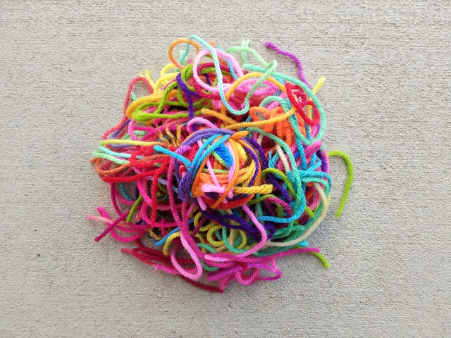 A nest of yarn scraps with a small yarn ball in the middle