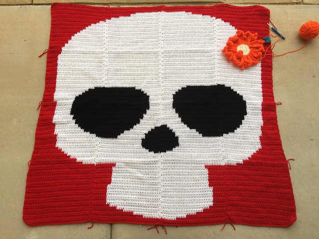 A Day of the Dead sugar skull yarn bomb with a large crochet daisy