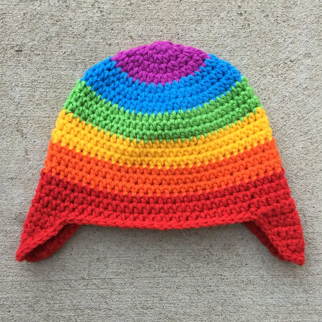 A rainbow inspired crochet hat with earflaps for a toddler