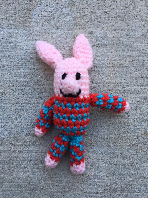 A small mini-meta crochet pig wearing blue and red pajamas.