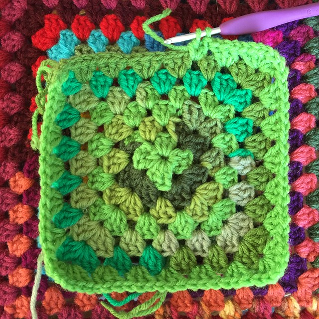 A very green crochet granny square made with yarn scraps