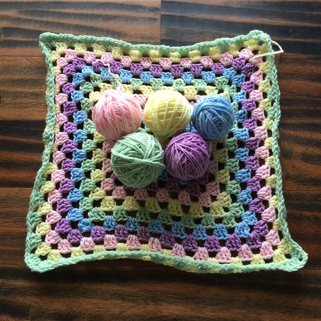 The yarn from three crochet granny squares, frogged for reuse, and a fourth granny square I unearthed.