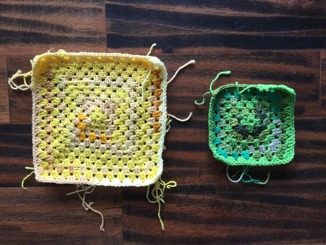 Two monochrome granny squares before adding onto them with more yarn scraps