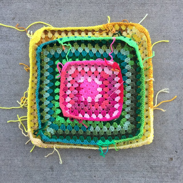 A pile of scrap yarn granny squares
