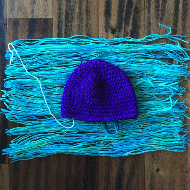 A purple crochet hat on top of lengths of yarn cut to attach to the hat to make troll hair
