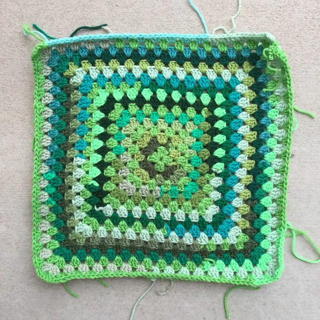 A green scrap yarn granny square