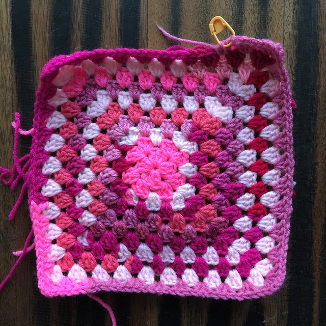The crochet square made of scraps of pink yarn after more rounds are added
