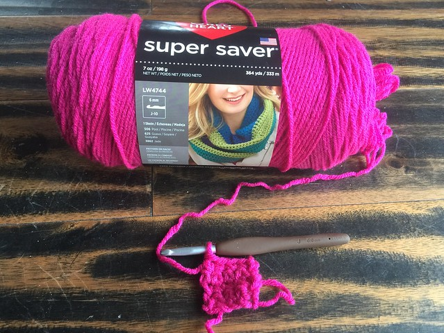 Making a crochet square using a skein of shocking pink yarn
