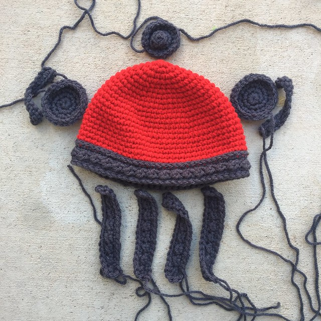 All of the pieces for a red and gray crochet Viking helmet for a baby