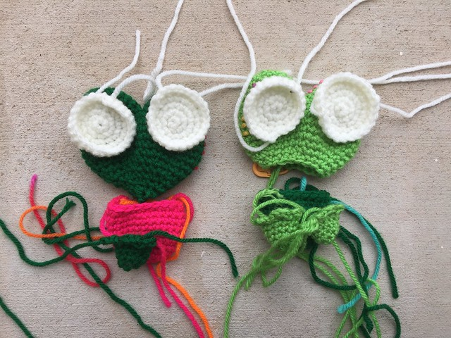 Two as-yet-to-be completed crochet frogs worked in two shades of green, and pink.
