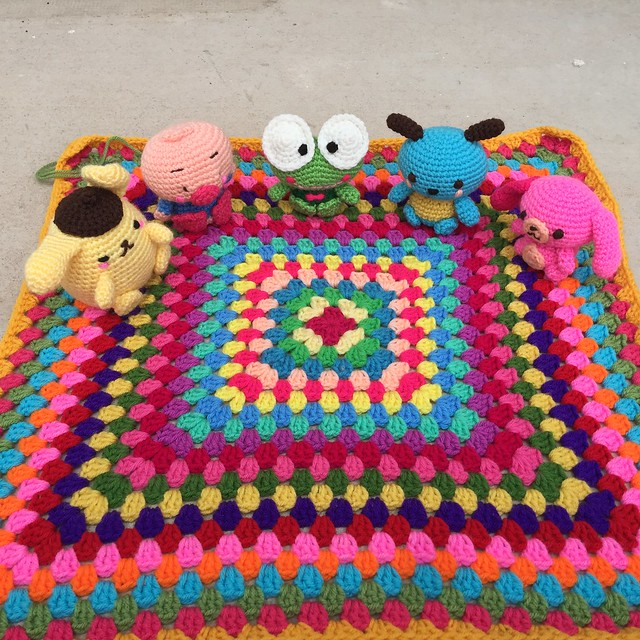 Six Hello Kitty amigurumi hang a picnic on a granny square blanket