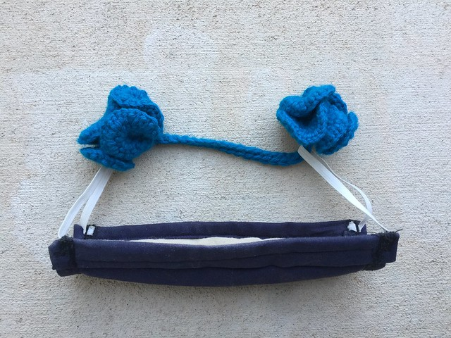 A hyperbolic crochet ear saver shown with a face mask