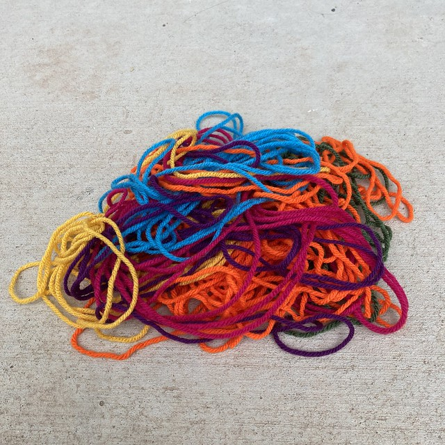 Eight strands of multiple colors of  yarn, each just a little over 13 feet long