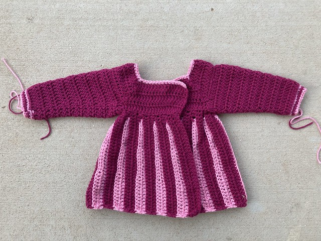 An almost completed pink and plum pleated crochet sweater