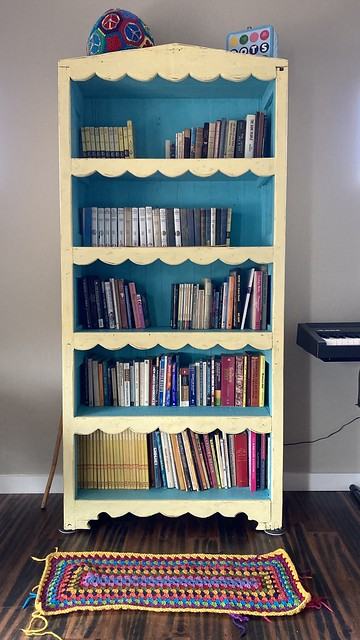 My new book case with the multicolor granny rectangle crochet rug in front of it after I have a change of heart
