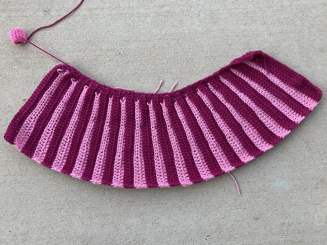 The pleated skirt portion of an Eloise crochet sweater