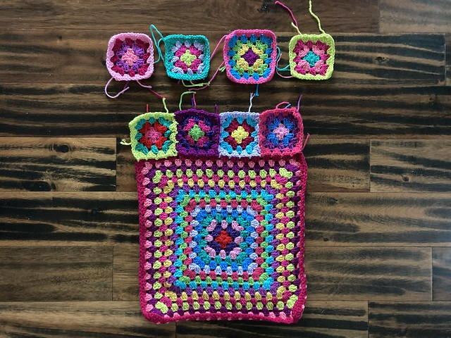 A multicolor granny square cardigan begins to take shape