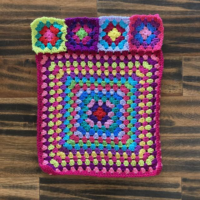 The back panel of a scrap yarn crochet cardigan