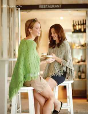 Two women enjoying a cup of coffee while wearing a crocheted poncho.