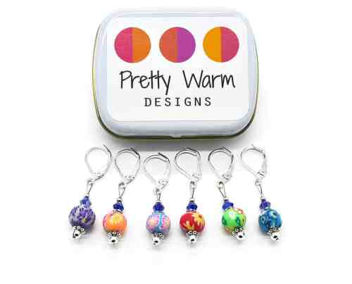 Photo of 6 Stitch Markers from Pretty Warm Designs in various colorful designs with a tin case