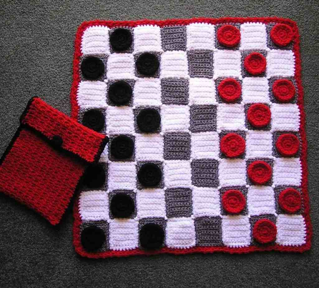 Photo of a crocheted checker board with black and red pieces with a red and black pouch