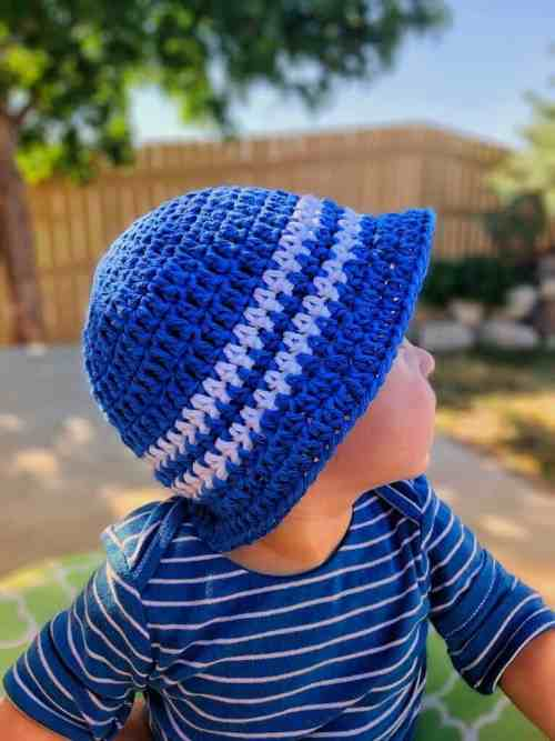blue with white stripes Sun and Sand Little Boys bucket hat, worn by a baby