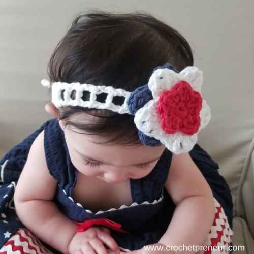 Photo of a baby wearing the white Summer Headband with blue, white, and red flower detail