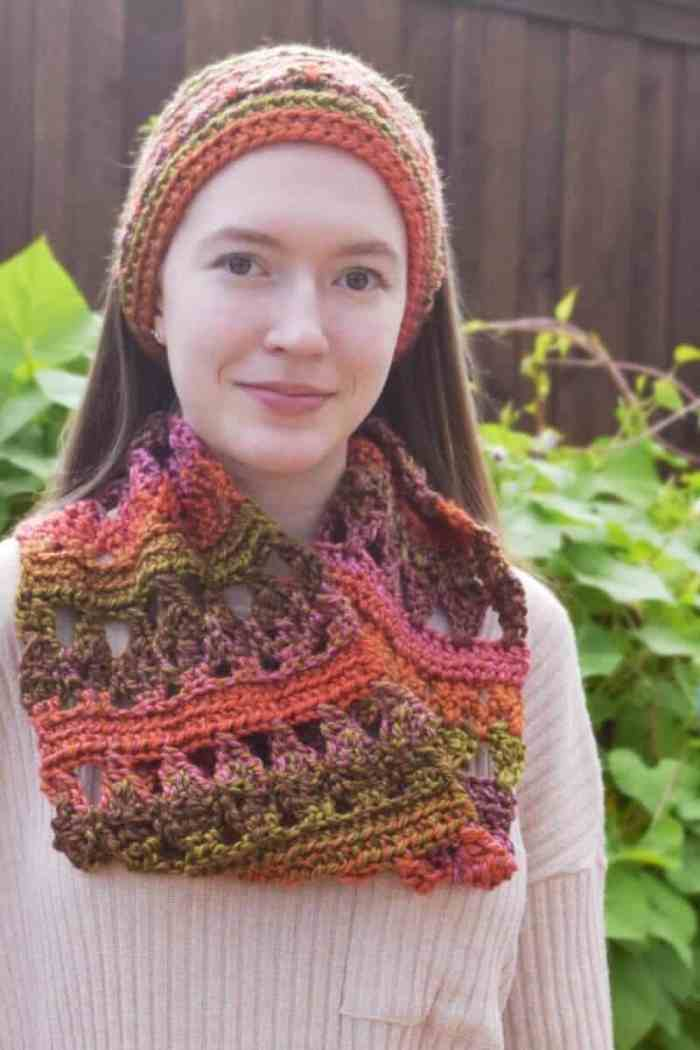 Photo of a woman wearing the colorful crocheted Autumn Adventure Cowl paired with a headband