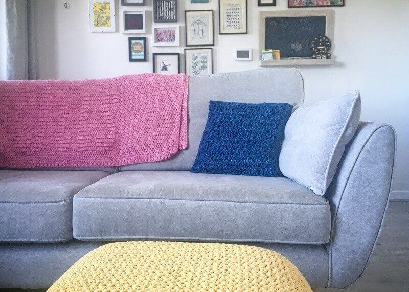 Photo of the crocheted blue building block pillow on a sofa in a living room