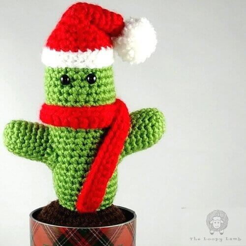 Image of the crocheted St. Prickolaus Cactus wearing a Santa hat and red scarf