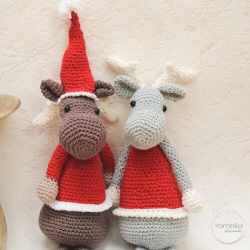 Photo of two crocheted Einar the Elk, one wearing a Santa hat and the other one wearing a reindeer headband
