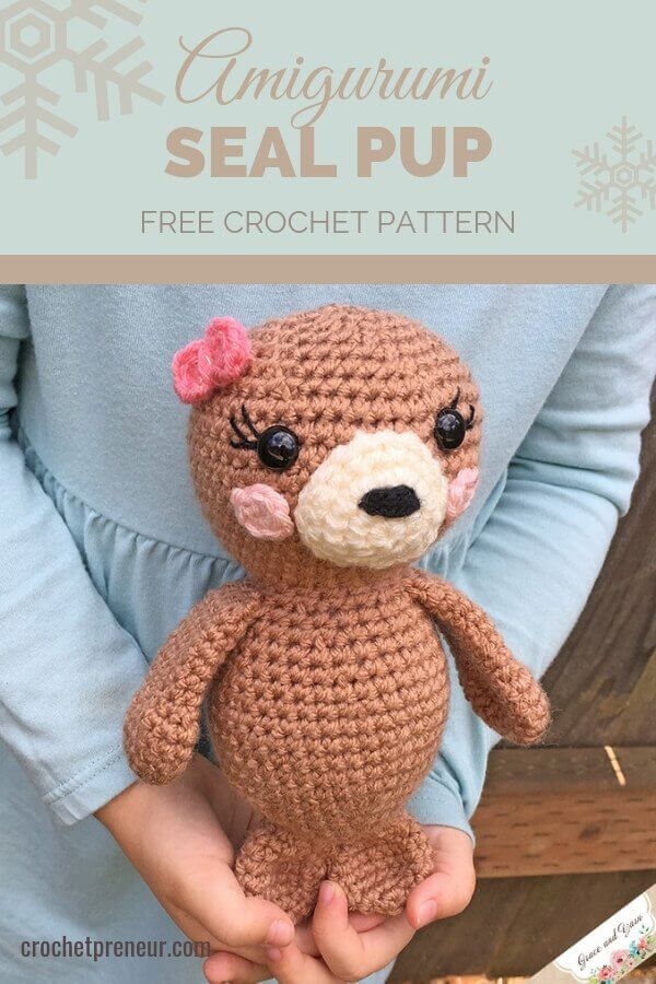 Pinterest graphic for Amigurumi Seal Pup FREE Crochet Pattern with a photo of the stuffed animal held by a pair of small hands