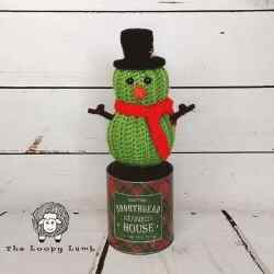 Photo of the crocheted Stanley the Cactus Snowman with a black top hat and red scarf standing on a tin can