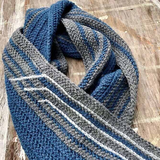 Photo of the Sleigh Ride Men's Scarf Free Crochet Pattern on a wooden plank