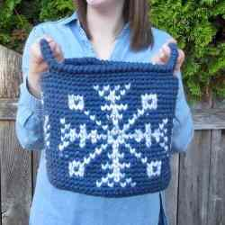 Photo of a woman holding the blue and white crocheted Let it Snow Basket