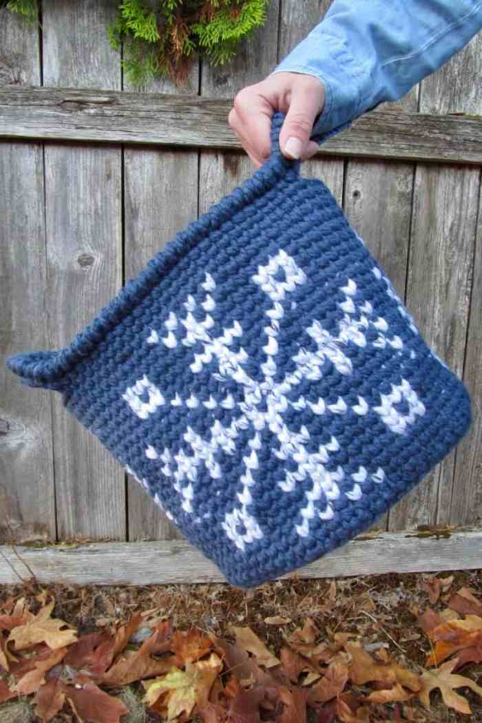 A photo of a hand holding the crocheted blue snowflake tapestry basket with dried leaves and a wood background