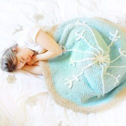 Photo of a sleeping woman using the warm crocheted Snowflake Sugar Cookie Blanket