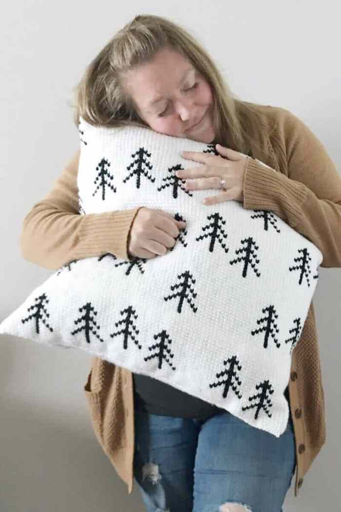 Photo of a woman hugging the Scandinavian designed FREE Nordic Tree Pillow Crochet Pattern