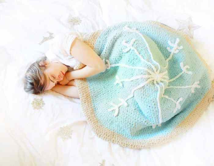 Photo of a sleeping woman covered with the Snowflake Sugar Cookie FREE Beginner Crochet Pattern