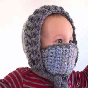 A baby wearing the Snow Day Hood winter hat with its detachable mask