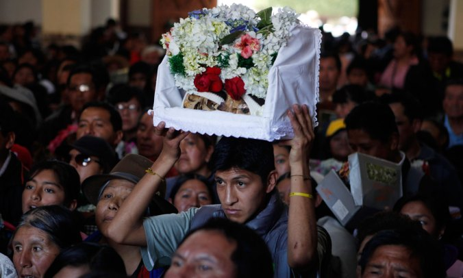 Family members carry ñatitas into a church