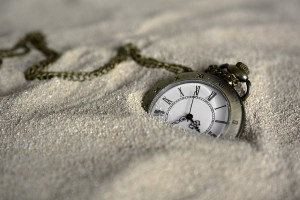 pocket watch emerging from the sand