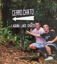 Un amigo y yo en cuclillas con el cartel de cerro Chato a nuestra derecha