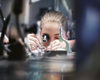 IWC young people lady girl woman watchmaker assembling work manufacture production working Schaffhausen sitting at table