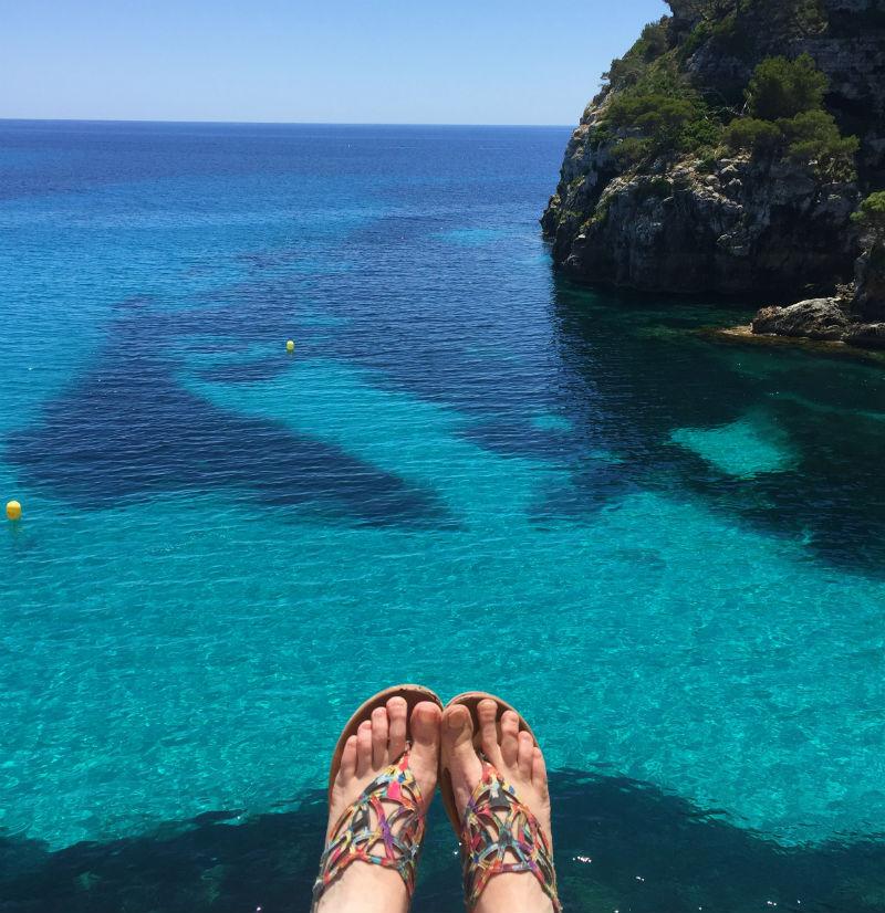 feet dangling near cliff Cala Macarelleta menorca spain