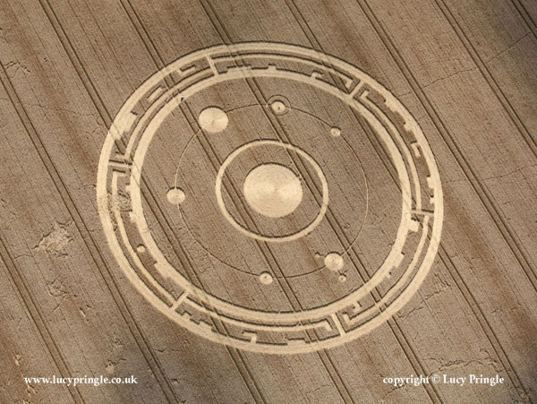 Maiden Castle, Dorchester, Dorset. 26 July 2015. Wheat. c.240 ft (73m) diameter. A concentric design with a 'sun' at its centre surrounded by a circle of flattened wheat. A fine circle denotes the path of six 'planets' some with 'satellites'. The design is bordered by a 'notched' design reminiscent of a complex cam or 'key' motif.