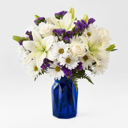beyond blue is mix of white and blue flowers in a deep blue glass vase