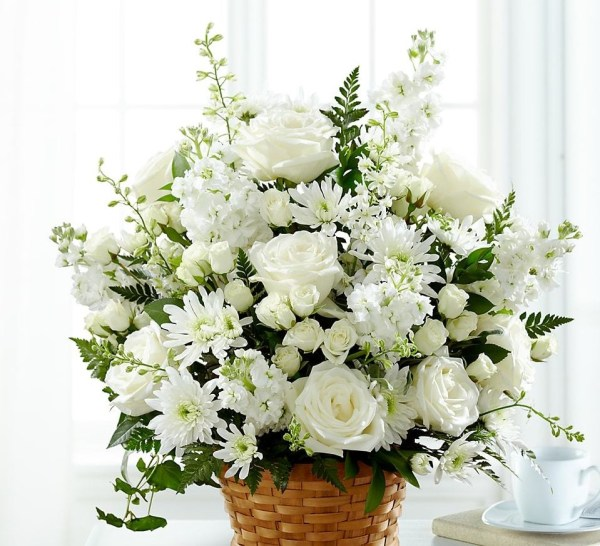 a mix of white flowers in a woven basket