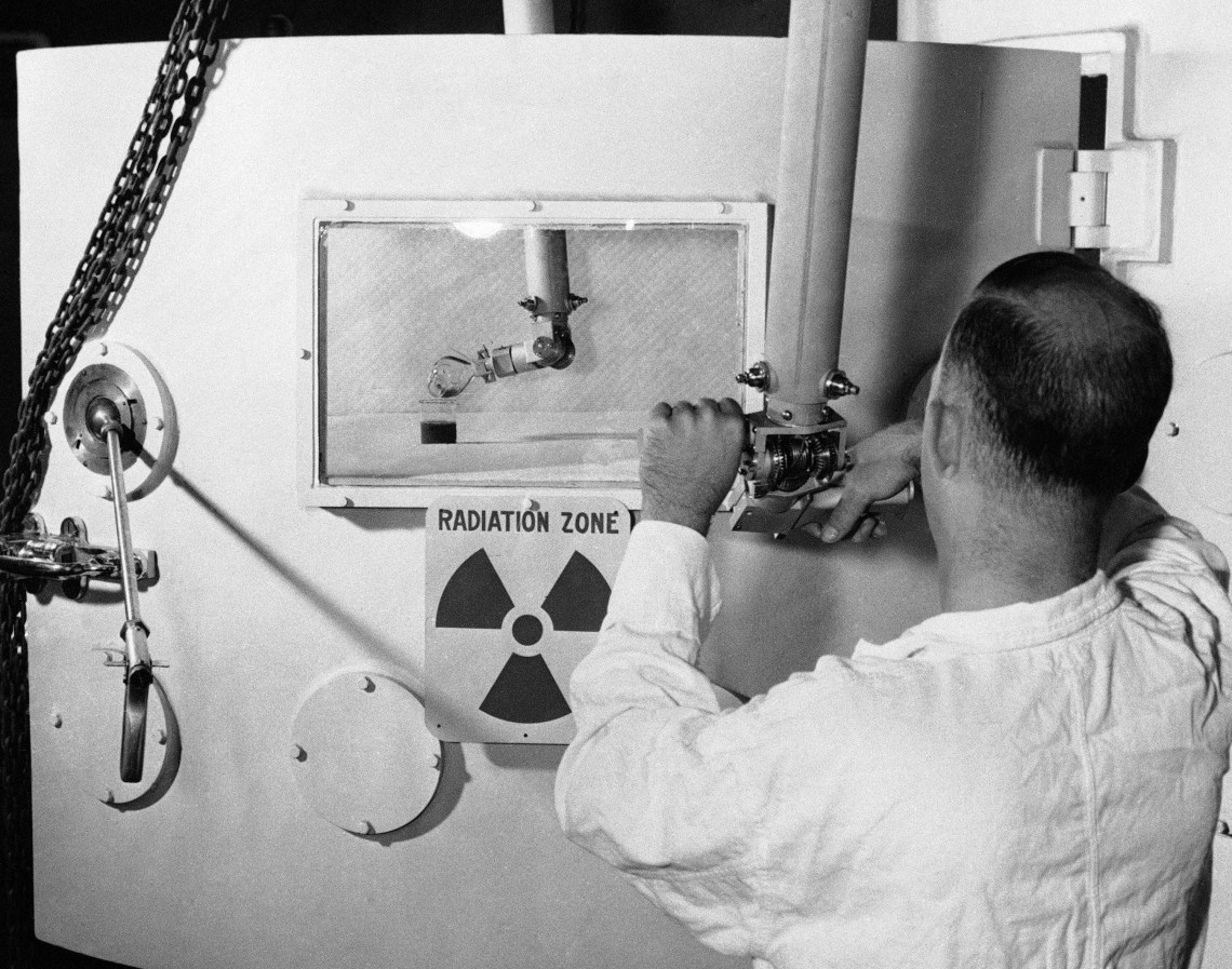 """A man works a lever in front of a sign that reads """"Radiation Zone"""""""