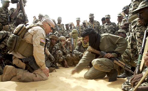 A U.S. Special Forces soldier instructs Malian troops in counterterrorism tactics through a translator (right, in black turban) on the outskirts of Timbuktu. Photographs by Justin Bishop.